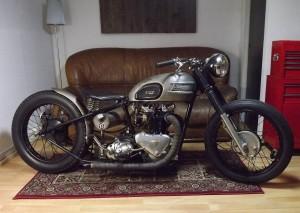 Moto Triumph bobber color metal sobre una alfombra persa en una sala con sofá y lampara