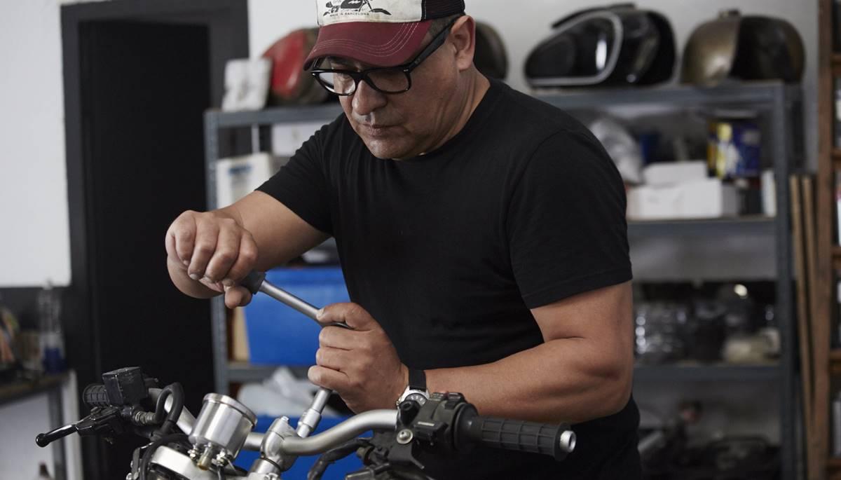Mecánico de motos ajustando un tornillo de manillar de una moto